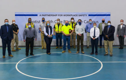 """A group of people gather in front of a banner that reads """"a partnership for workplace safety"""""""