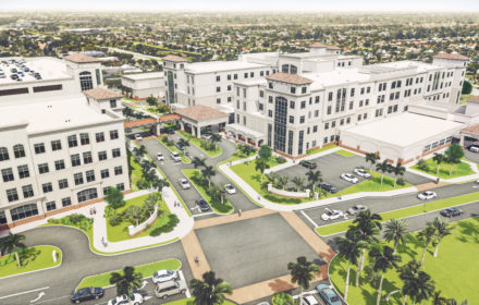 An artist's rendering of a hospital building surrounded by palm trees