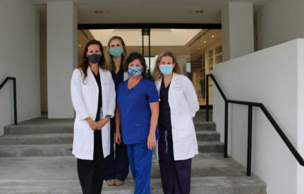 Four medical professionals wearing fabric face coverings gather in front of a medical office building