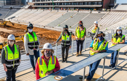 A group of women in hard hats and safety vests stand inside an under-construction football stadium