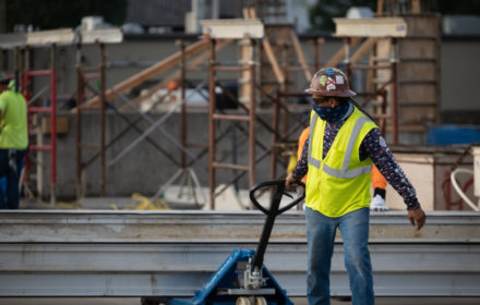A man in construction personal protection equipment works on a jobsite