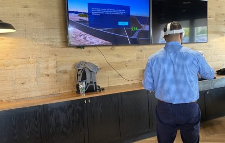 A man wearing a virtual-reality headset with a safety simulation shown on a television screen