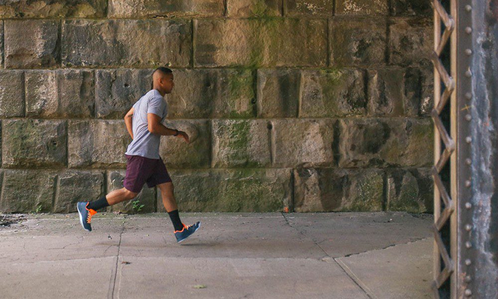 a male runner jogs across past a grey concrete wall