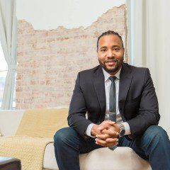 Deon Gordon in a business suit sits on a couch in a building in downtown Birmingham, Alabama