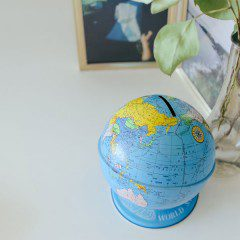 a tin globe on a white desk in a beautiful office