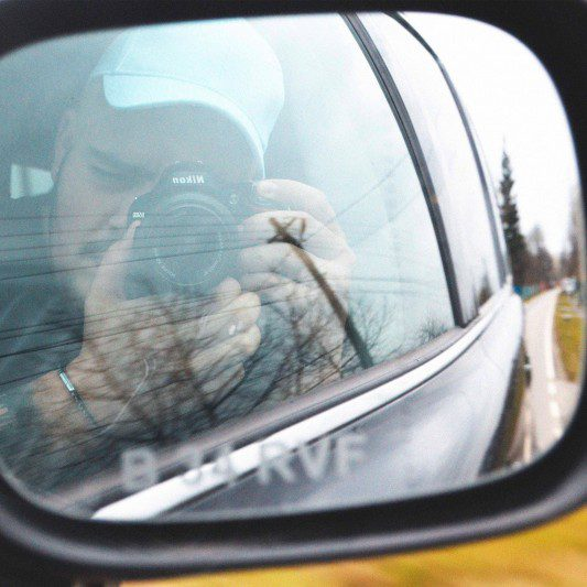 man takes a photo of a car mirror from inside the car