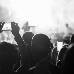 black and white photo of a man records an outdoor concert on his IPhone