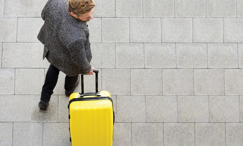 man carries bright yellow suitcase