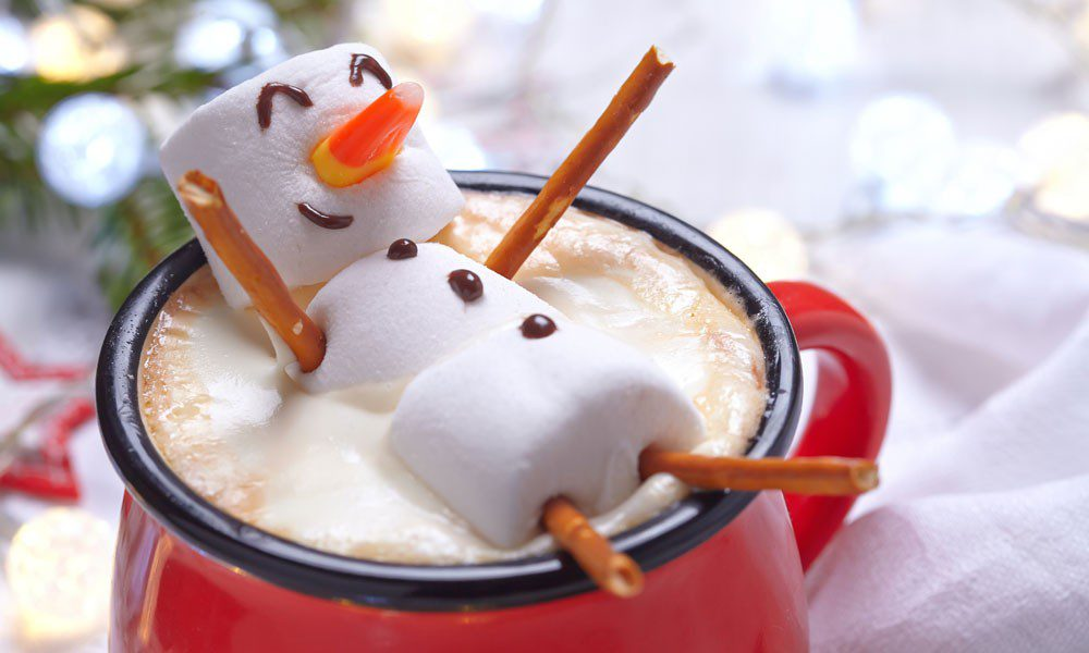cute marshmallow man lays in a cup of hot cocoa on a table decorated for Christmas