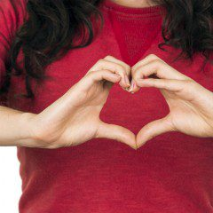 girl makes heart symbol with hands