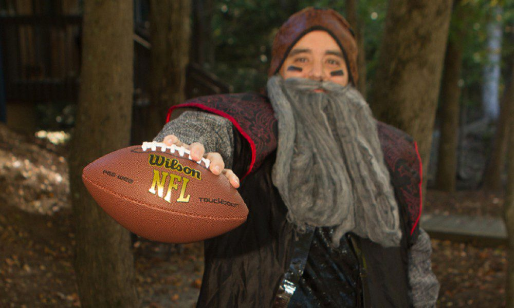 man dressed as a fantasy character holding a football for infomedia's Halloween costume contest