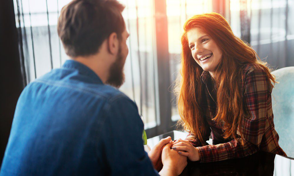 red headed woman holds hands with a man on a first date