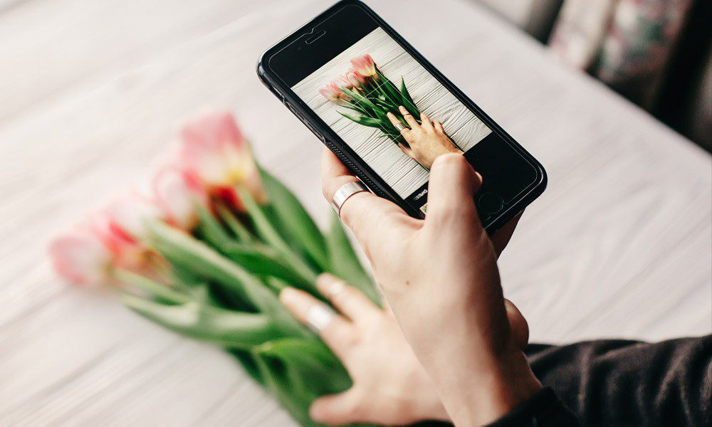 Woman taking a photo of flowers with her phone