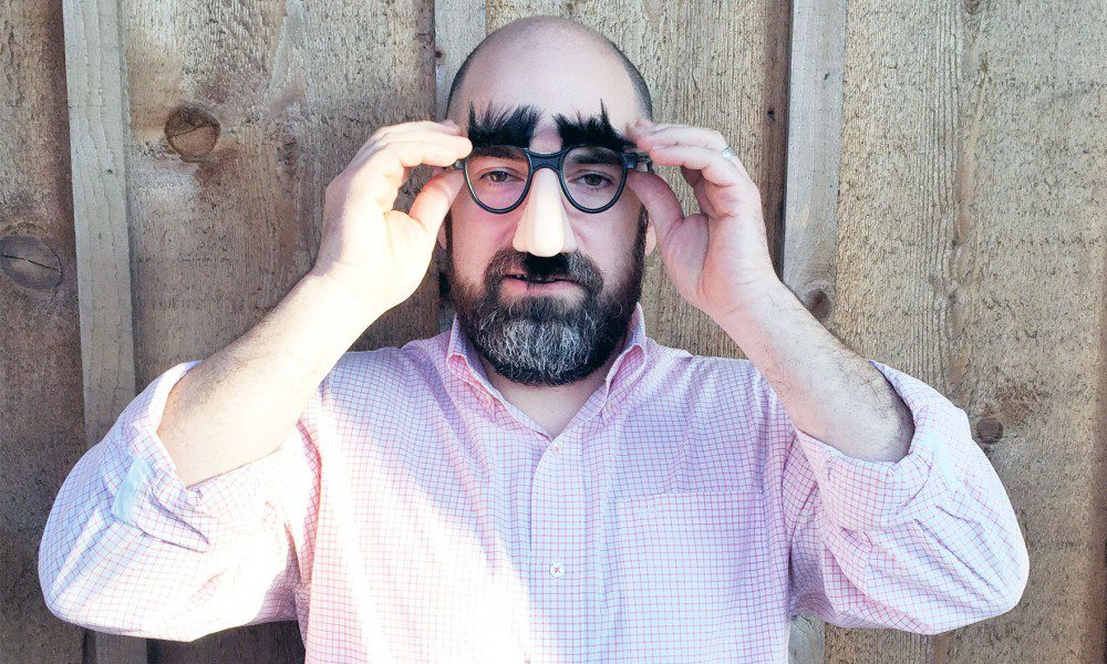 Jason Lovoy, president of Infomedia, wheres silly glasses with a fake nose and eyebrows outside of the Infomedia office building