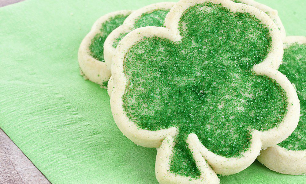 Four leaf clover-shaped sugar cookies decorated with green sugar crystals