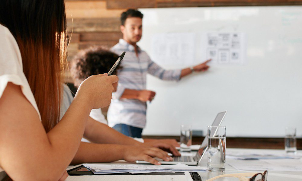 woman raises her pen as a fellow coworker presents wireframes on a white board
