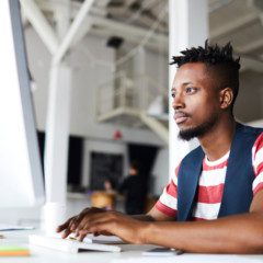 young african american man works on a desktop computer