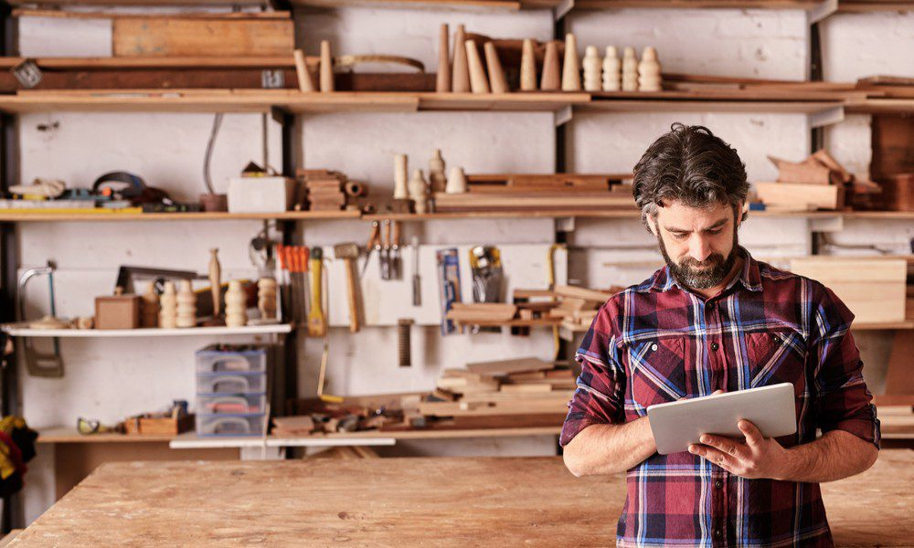 bearded man stands holding an ipad in an artisan wood working shop