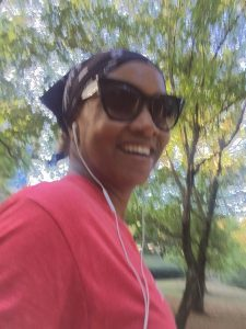 Woman smiles while listening to music on a walk