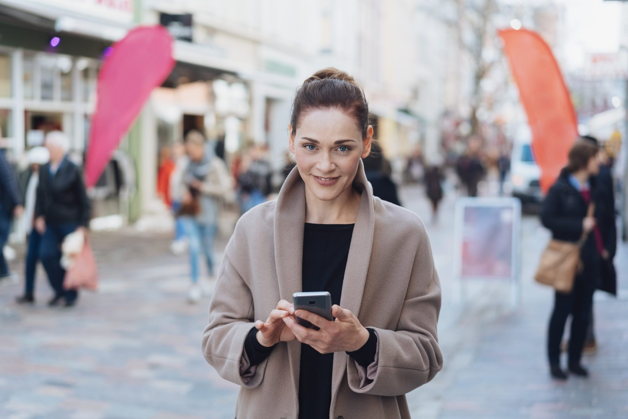 Street portrait of young smiling woman wearing grey coat using phone